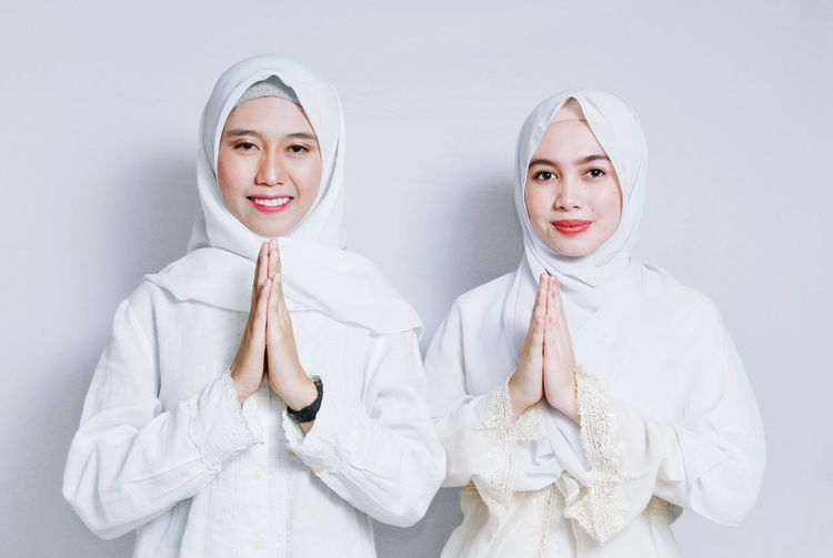 Portrait of smiling women wearing hijabs greeting against white background