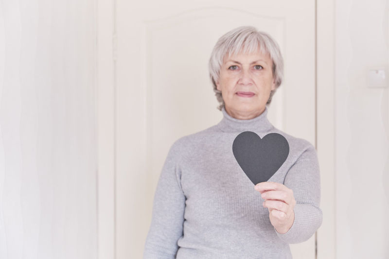 Portrait of mature woman holding heart shape standing against wall