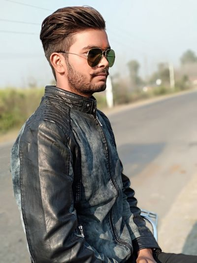 Young Man Wearing Sunglasses While Standing On Road Against Sky