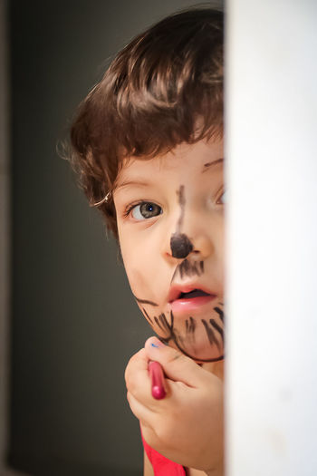 Close-up portrait of boy with face paint hiding behind wall