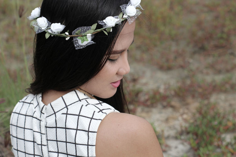 Close-up of beautiful woman wearing wreath outdoors