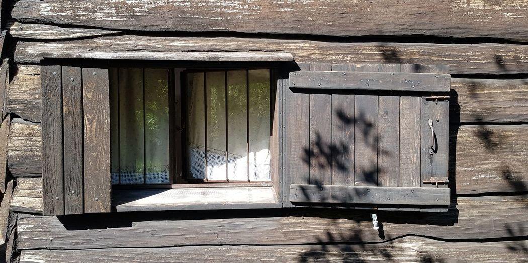 Close-up of open window on wooden door of building