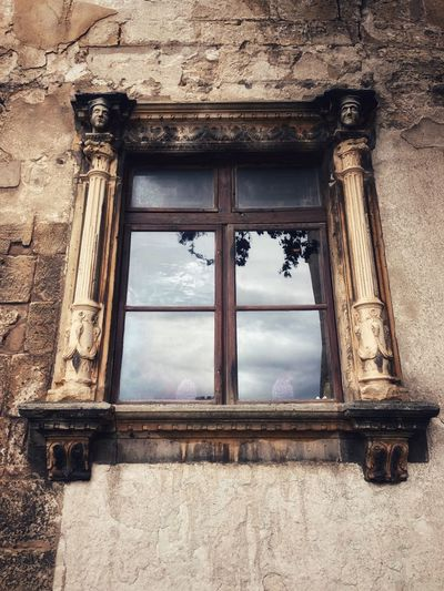 Old window with a wooden frame, framed by beautiful stone carvings with sculpted elements in the form of columns and figures on the peeling stone wall of a medieval building Architecture Medieval Architecture Medieval Window Built Structure Architecture Window Building Exterior Day No People Building Glass - Material Outdoors Wall - Building Feature Low Angle View Closed Old House My Best Photo My Best Photo