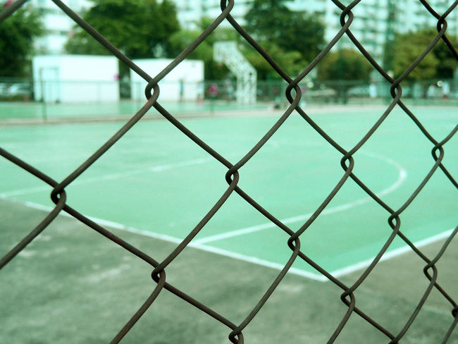 Metal mesh wire fence with blur basketball court background. Grid Mesh Barrier Boundary Chainlink Fence Crisscross Fence Field Guard Mesh Wire Fence Metal Play Playground Protection Safety Security