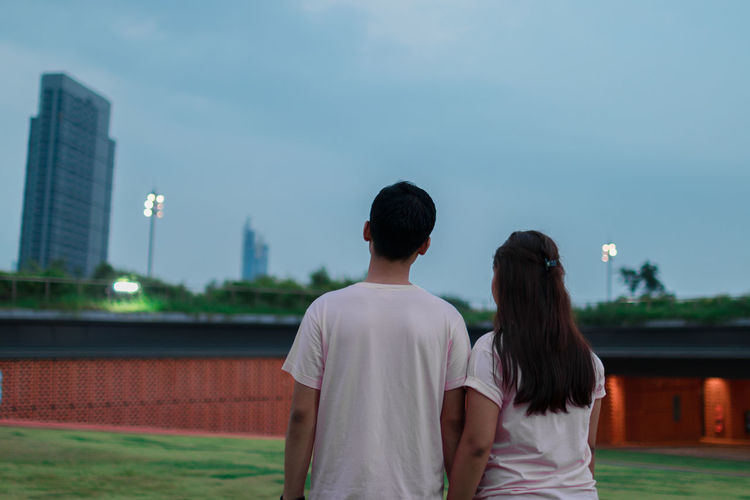 Rear view of couple standing in city against sky
