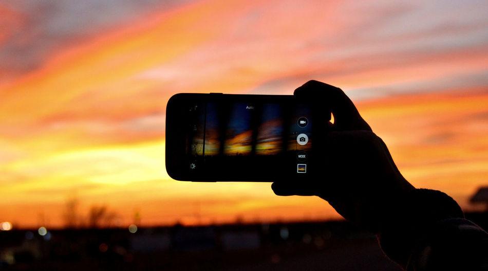 Man photographing through smart phone at sunset