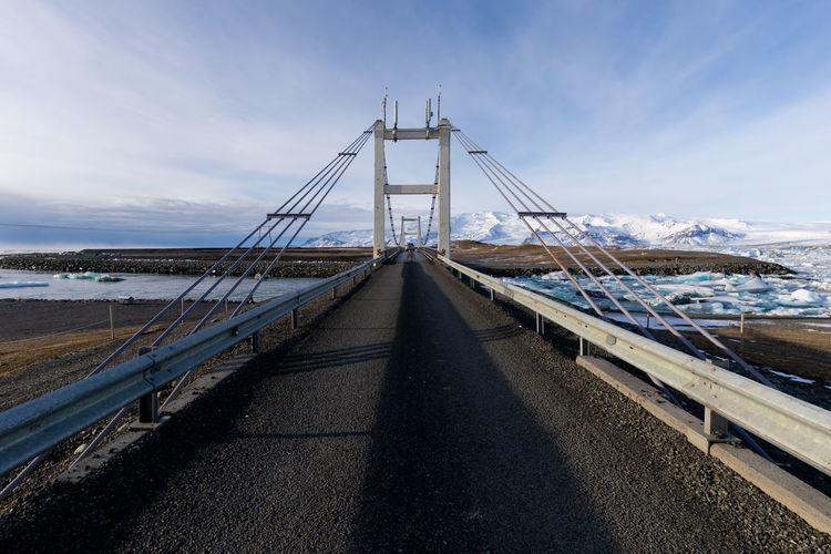 View of bridge over calm sea against sky