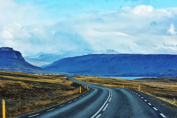 Diminishing Perspective Of Road Leading Towards Mountains Against Cloudy Sky