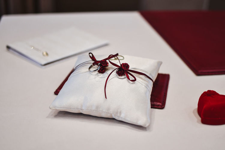 Indoors  Paper Gift Table Red Close-up No People Ribbon - Sewing Item Emotion Celebration Ribbon Still Life Box - Container High Angle View Box Bow Tied Bow Gift Box Christmas Present Holiday Wrapping Paper Luxury Wedding Rings