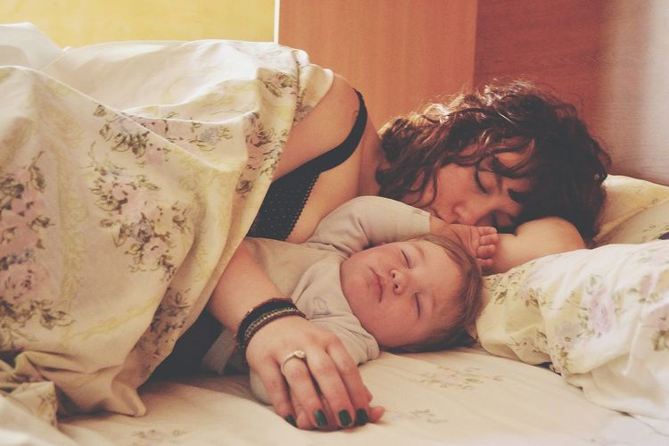 Mother with son sleeping on bed at home