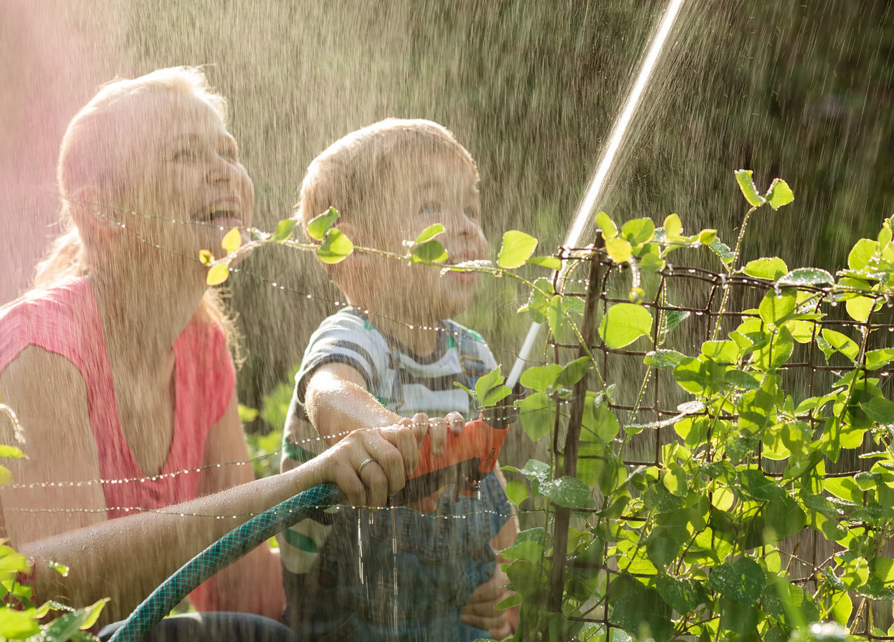 water, outdoors, togetherness, day, childhood, girls, boys, spraying, leisure activity, casual clothing, real people, two people, child, bonding, lifestyles, blond hair, nature, people