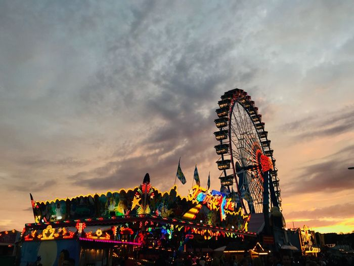 Low angle view of illuminated ferris wheel against cloudy sky