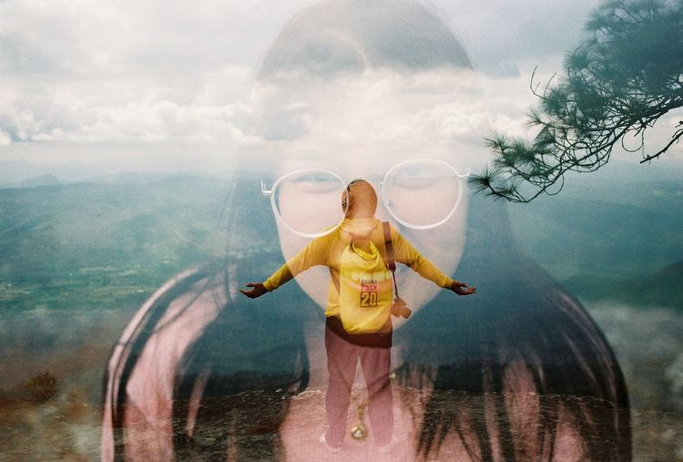 Digital composite image of woman standing on mountain against sky