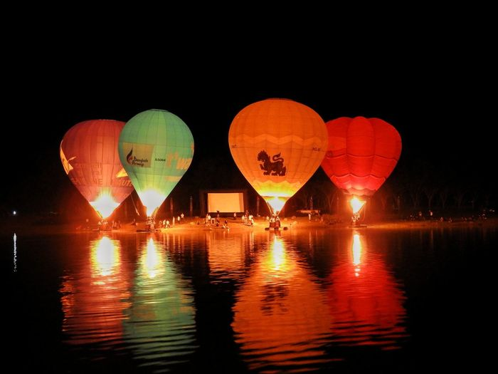 Illuminated hot air balloon flying over river against sky at night