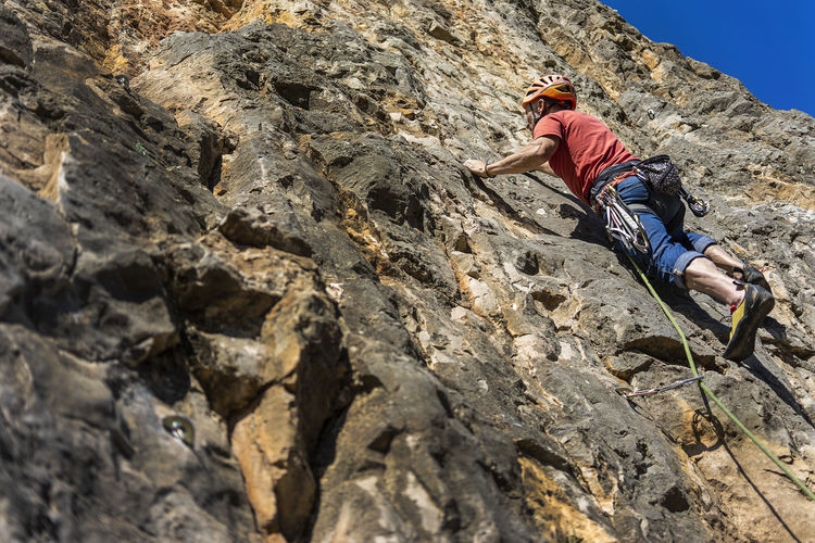 Climbing Rock Extreme Sports Rock Climbing Adventure RISK Safety Rope Strength Protection Low Angle View Rock Formation Determination Skill  Safety Harness Effort Outdoors Climber Climbing A Mountain Sport Climbing