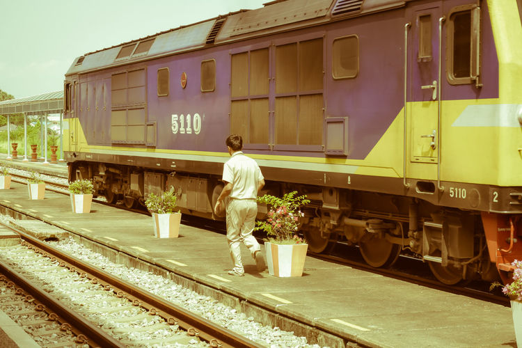 Man standing by train at railroad station