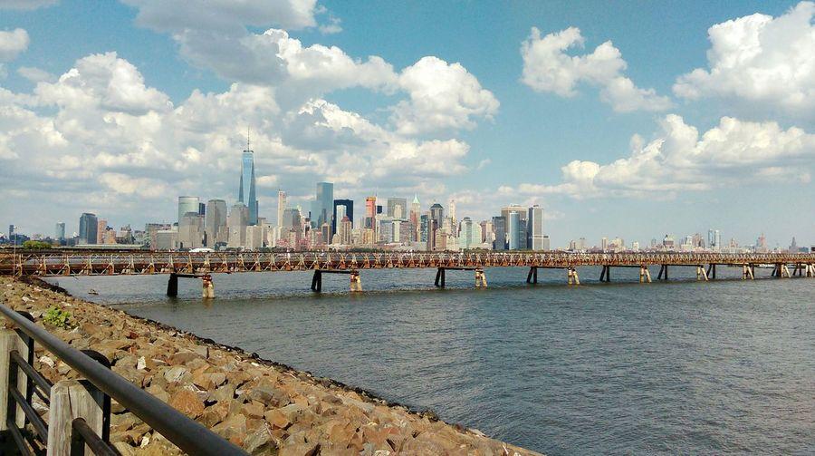 Footbridge over river by city against sky