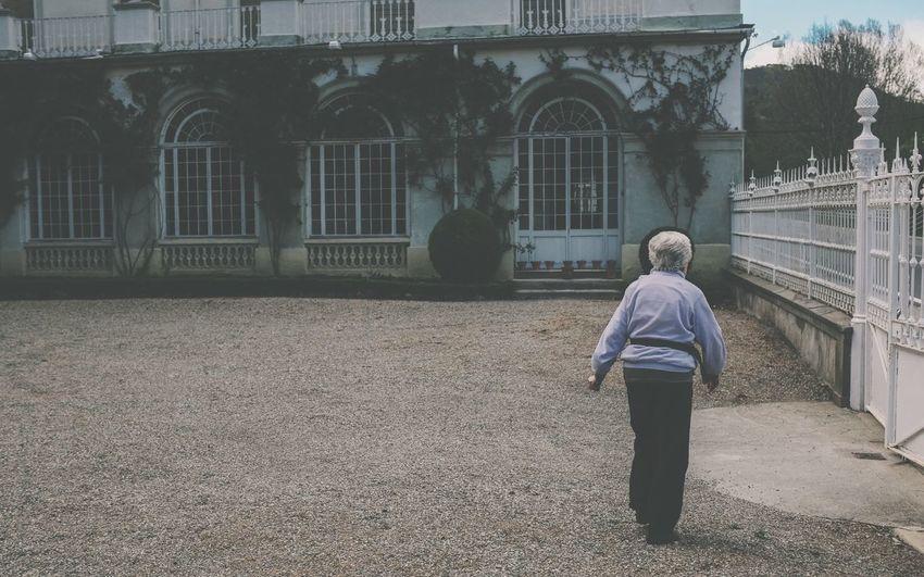 Rear View Full Length Of Senior Woman Walking In Yard