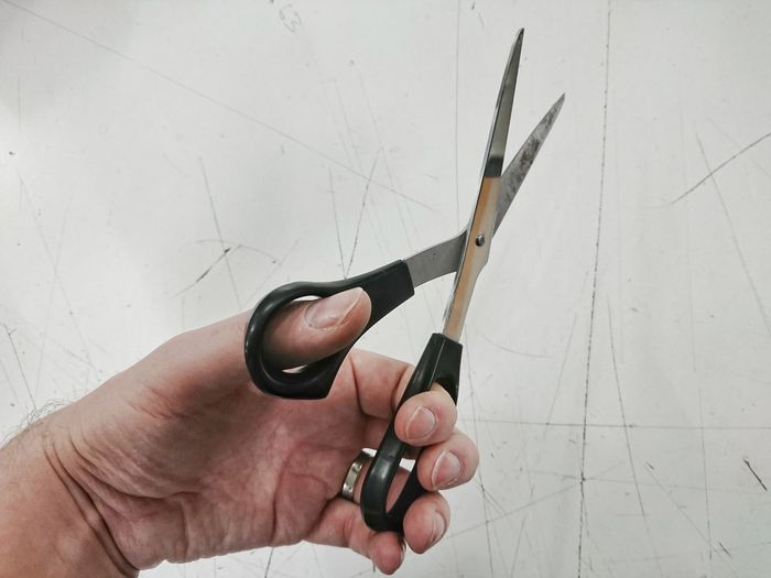 Cropped hand of man holding scissors by white wall