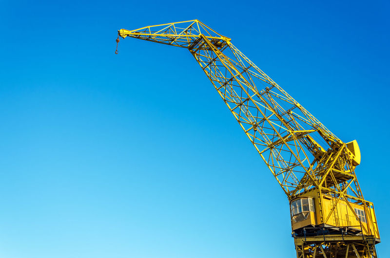 Low Angle View Of Old Yellow Crane Against Clear Blue Sky