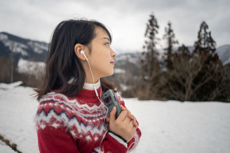 Young woman looking away while listening music over mobile phone during winter against sky