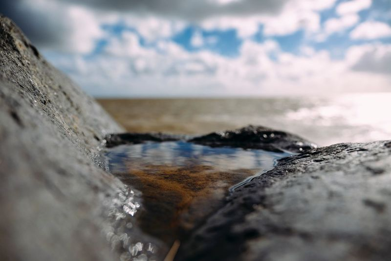 Reflecting Sea Horizon Over Water Water Beach Selective Focus Rock - Object Tranquil Scene Scenics Beauty In Nature Cloud - Sky Shore Tranquility Sky Rocky Nature Seascape Surface Level Non-urban Scene Day Focus On Foreground Nature Stone Outdoors