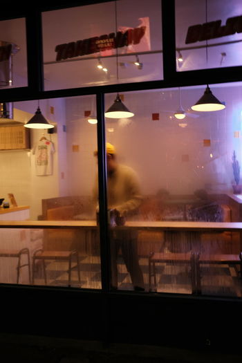 Reflection of illuminated glass window in restaurant