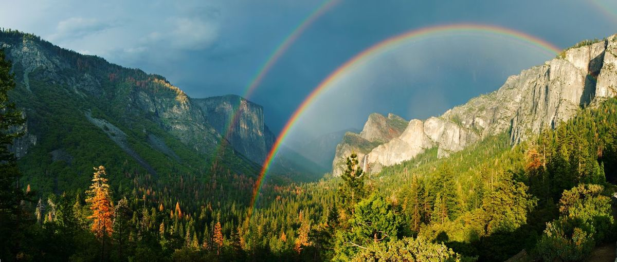 Scenic view of double rainbow and mountains against dramatic sky