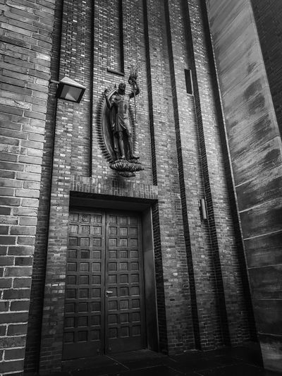 Church entrance... Textures and Surfaces Closed Door Christianity Church Church Entrance City Marketing Germany Sightseeing Spot Travel Tourism Travel Destinations Religion Architecture Sacred Faith Frog Perspective Close-up In Front Brick Building Monumental Buildings Black And White Architecture Built Structure Building Exterior Statue Sculpture Sculpted Historic Male Likeness Jesus Christ Angel