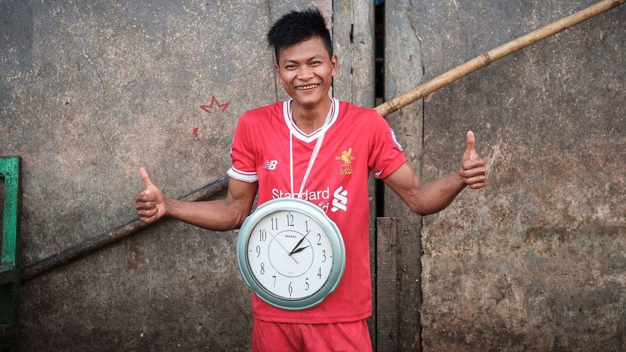 The clock man at the San Pya Wholesale fish market in Yangon Myanmar Myanmar Yangon Documentary Smiling One Person Clock Leisure Activity Wall - Building Feature Young Adult Standing Portrait Real People Lifestyles