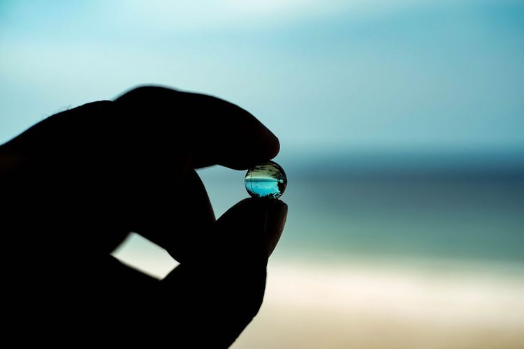 Close-up of silhouette hand holding crystal ball against sea and sky