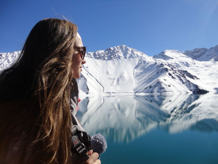 Woman Looking At Lake And Snowcapped Mountains