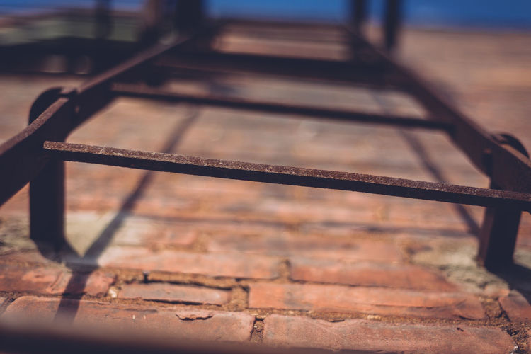 Low angle view of rusty ladder on brick wall