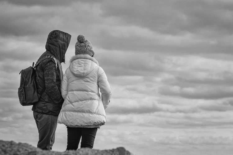 Rear view of couple standing against cloudy sky