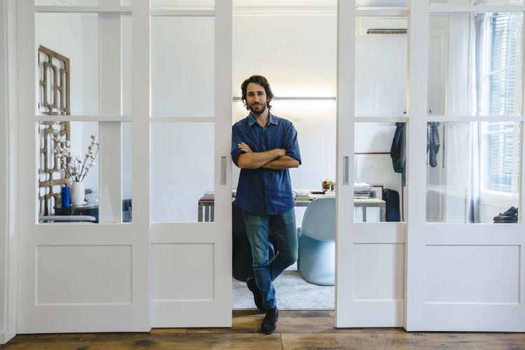 Portrait of man standing against door at home