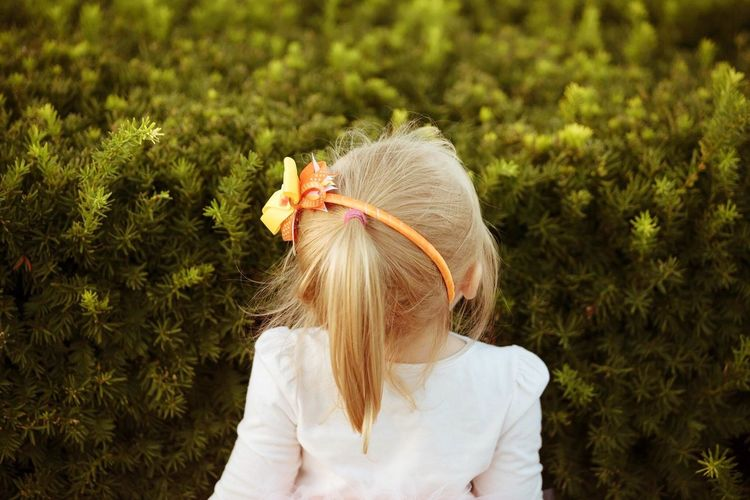 Rear view of girl standing against plants
