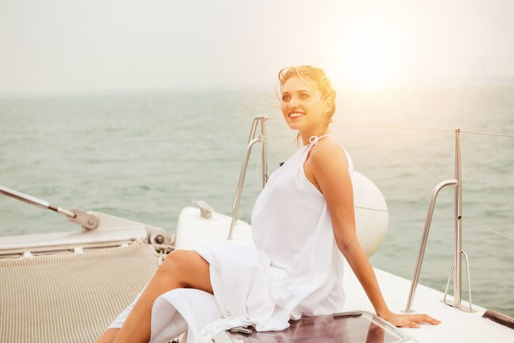 Young woman sitting on boat against sea against sky