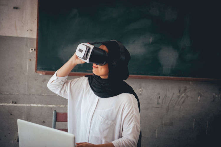Female Teacher Using Virtual Reality Simulator In Classroom