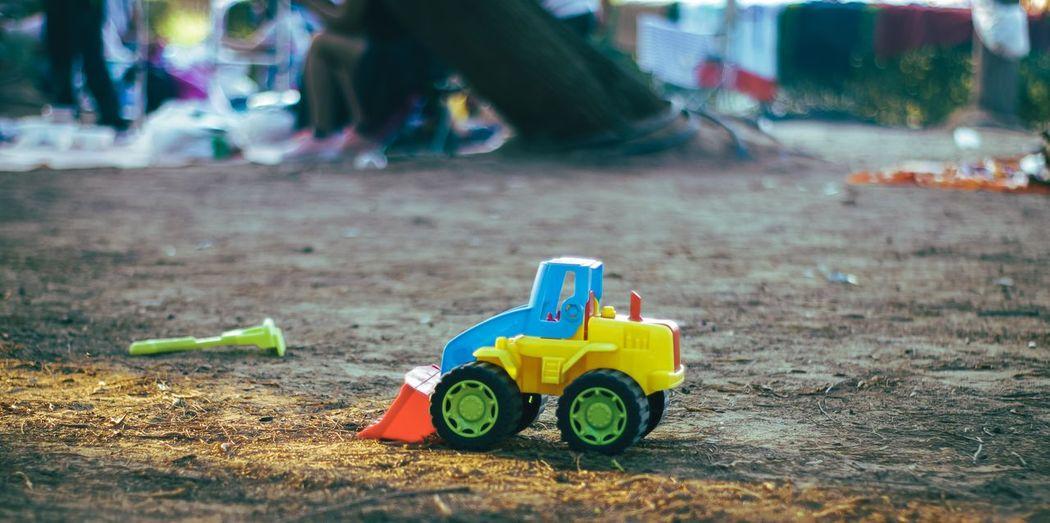 Multi colored toy bulldozer on land