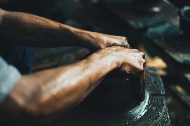 Cropped hands of man making pot at workshop