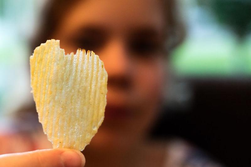 Woman holding heart shape potato chip