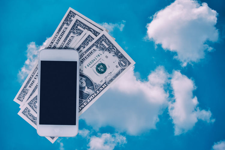 Digital composite image of mobile phone with paper currencies against cloudy sky