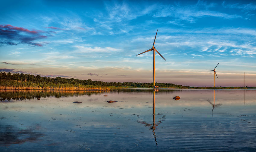 Scenic view of lake with wind turbines against sky during sunset