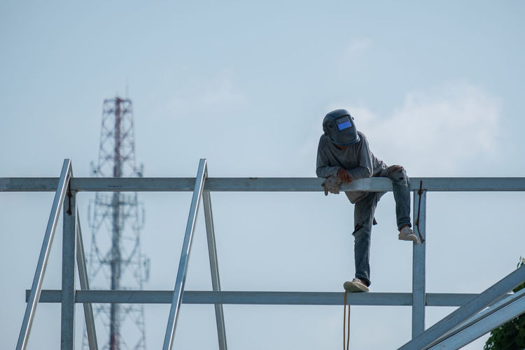 Low angle view of worker on metallic structure against sky