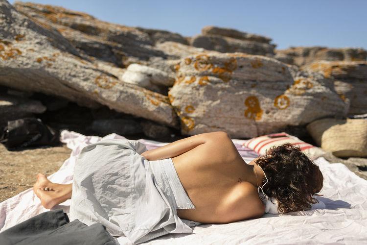 Woman lying on rock