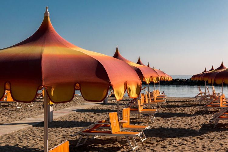 Parasols and sunbeds in Torre Pedrera near Rimini in Italy Badeort Strand Urlaub Baden Beach Beauty In Nature Clear Sky Day Nature No People Orange Color Outdoors Parasol Protection Roof Sand Sea Sky Sonnenliegen Sonnenschirm Sunlight Torre Pedrera Tranquil Scene Tranquility Water