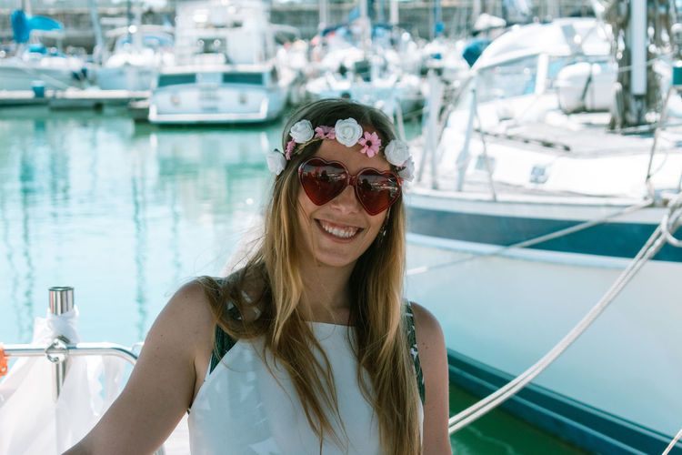 Portrait of smiling young woman wearing sunglasses at harbor