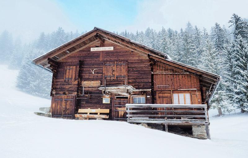 House on snow field against sky