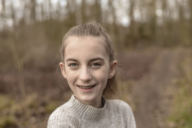 Close-up portrait of smiling teenage girl in forest