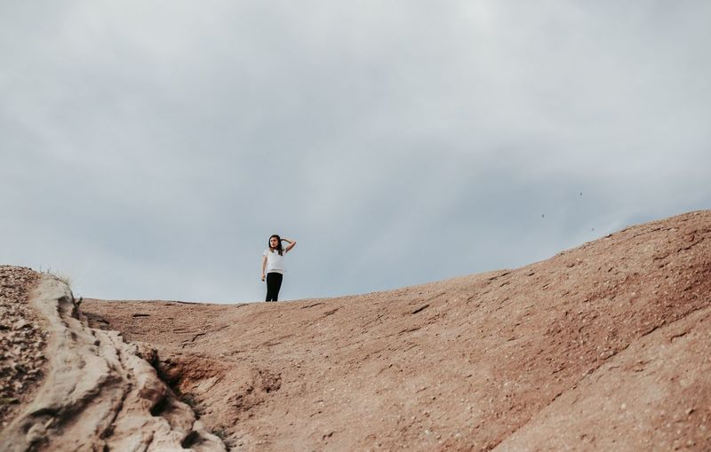 Low angle view of girl standing on mountain against cloudy sky